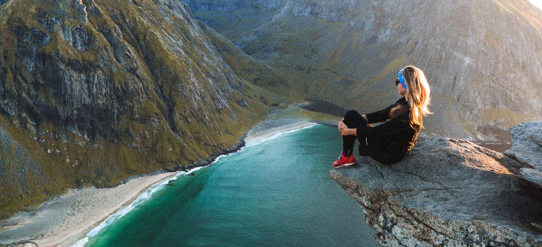 En kvinne ytterst på en fjellvegg med fjell og sjø i bakgrunnen