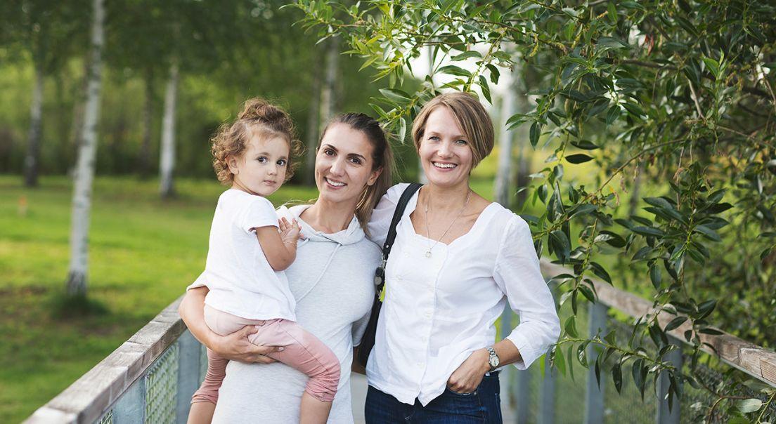 To kvinner og et barn i grønne omgivelser
