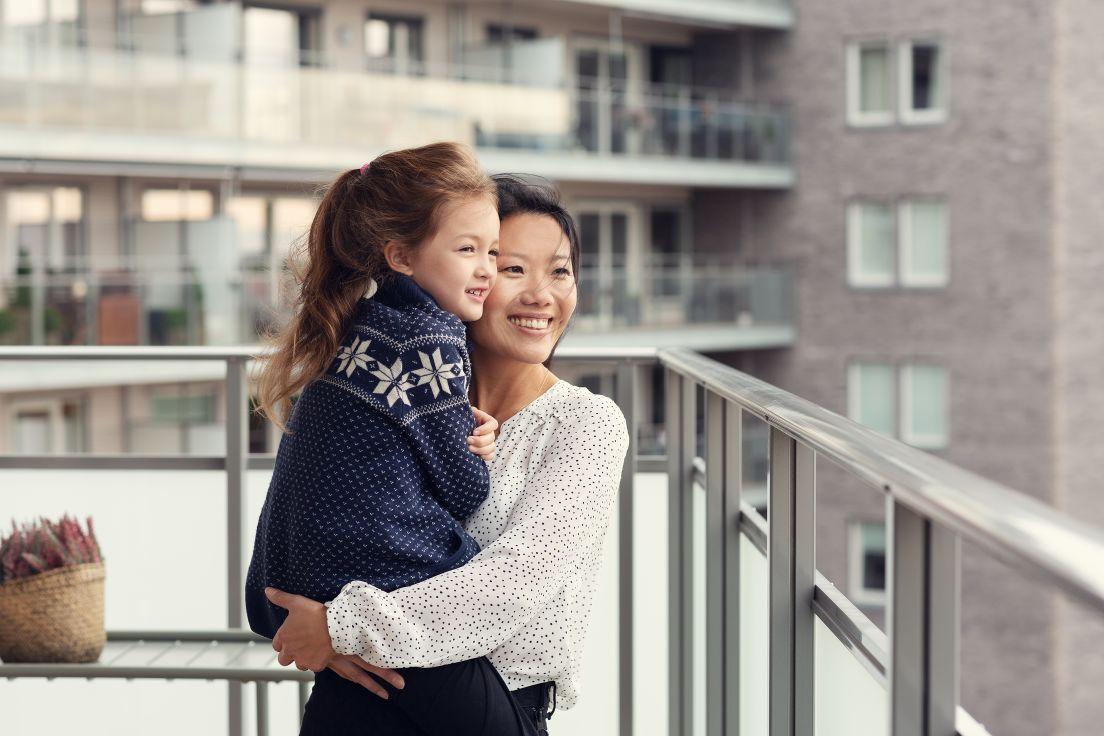 Mor holder datter i armene ute på balkongen sin