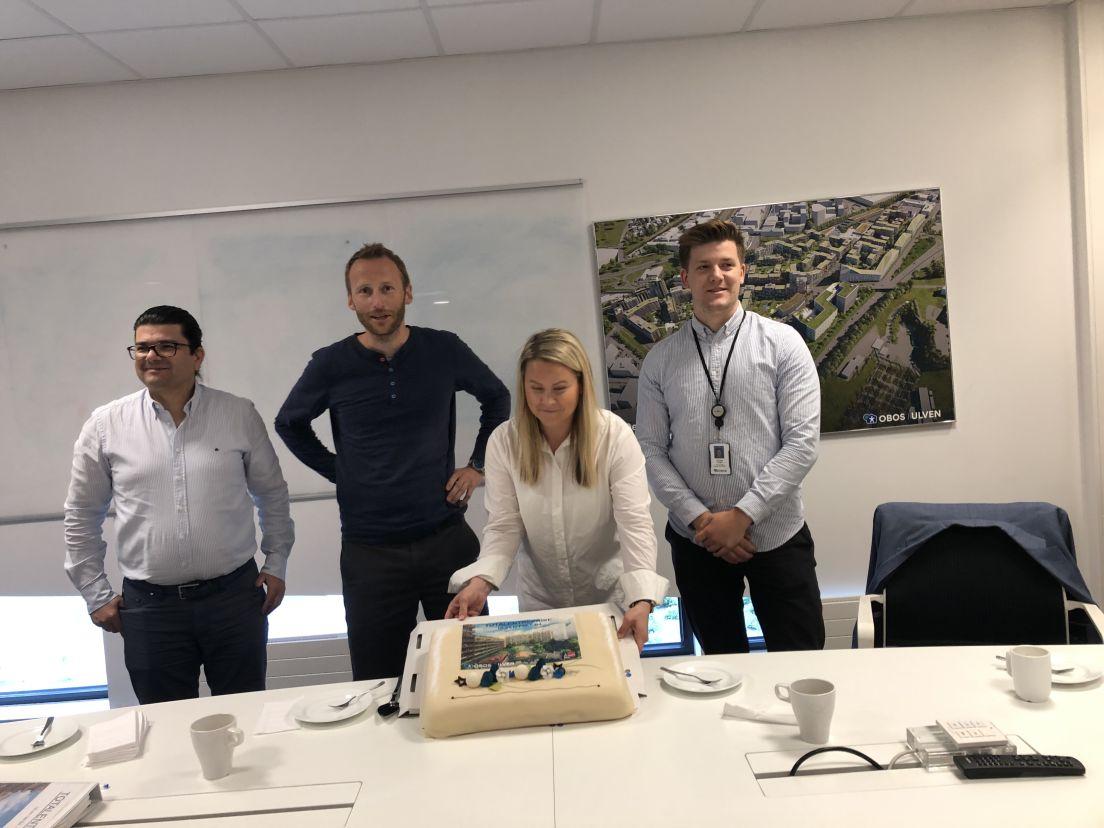 Bilde av fire personer ved signering og kake