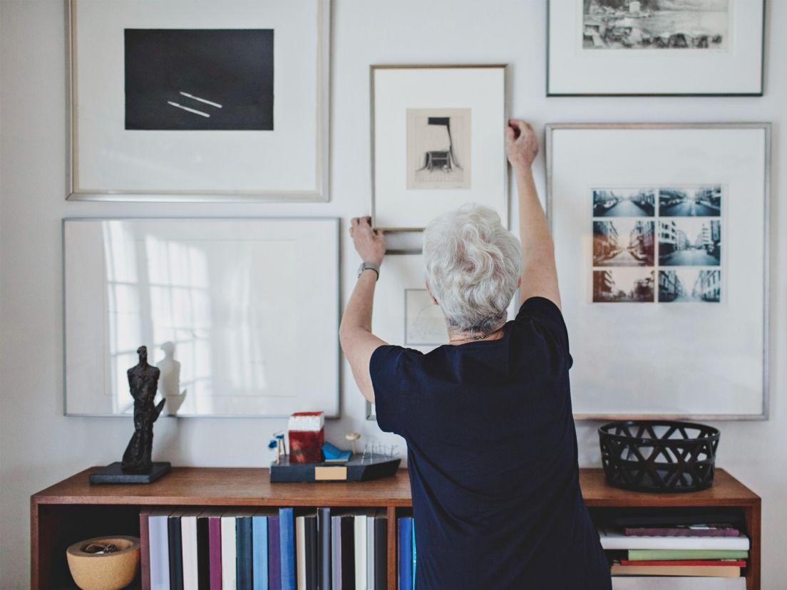 en äldre dam hänger upp tavlor på en tavelvägg