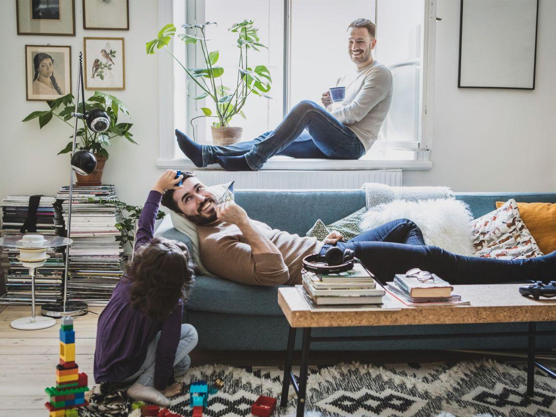 ett par med sitt barn sitter i sitt vardagsrum och tar det lugnt