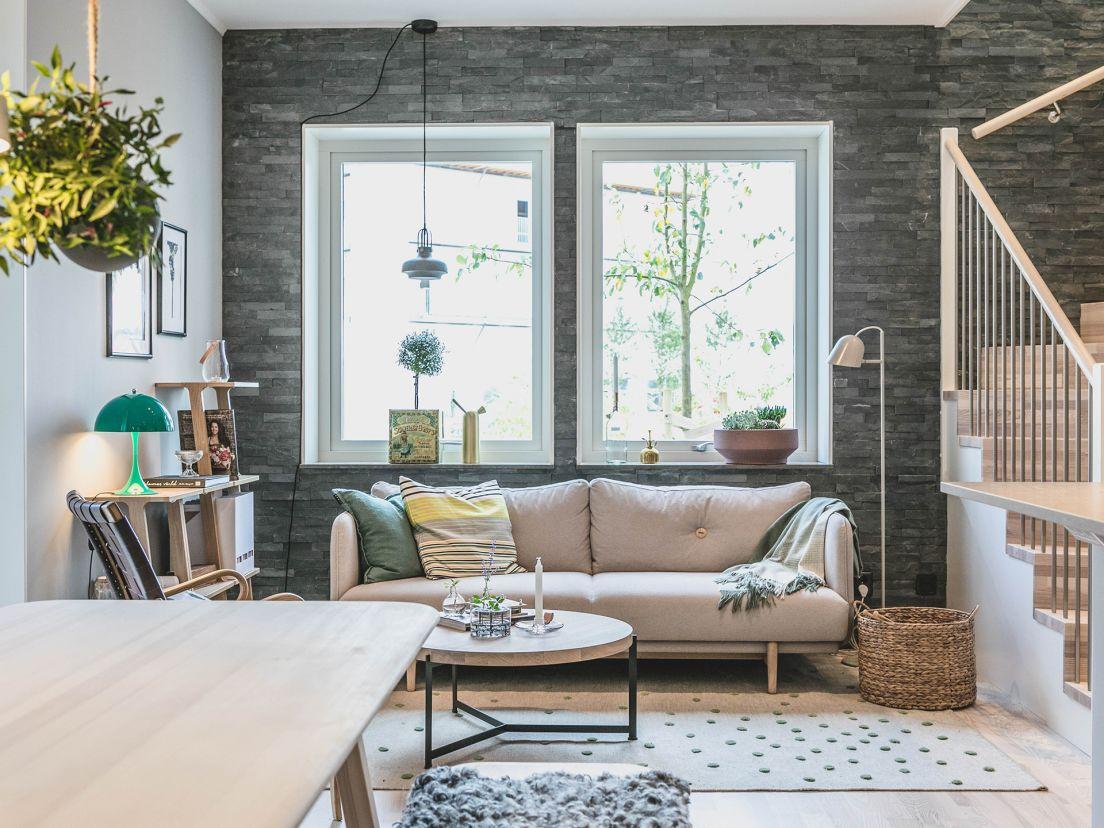 ett vardagsrum med en vit soffa och en taklampa