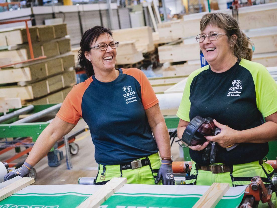 Två skrattande damer som arbetar i en OBOS-fabrik