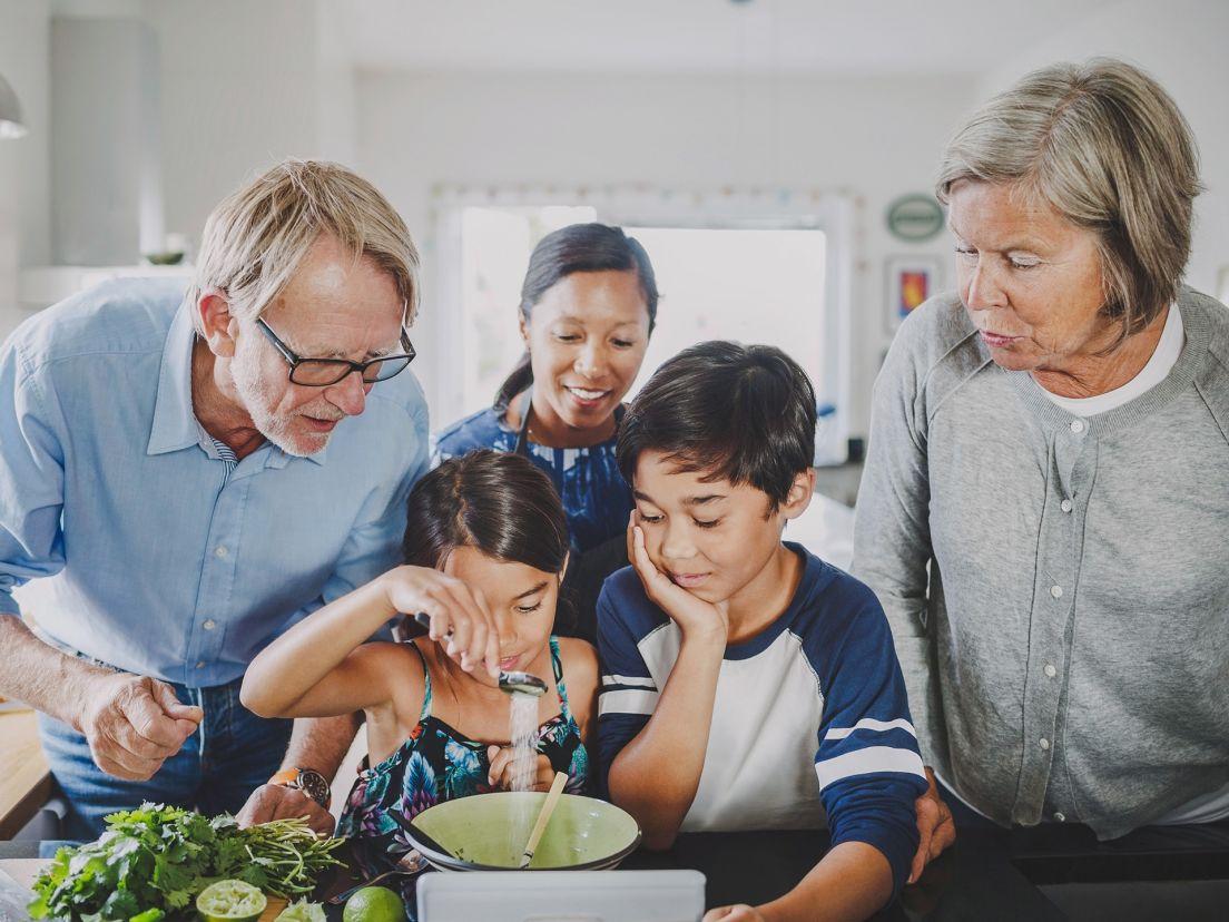 En familj på fyra personer lagar mat tillsammans