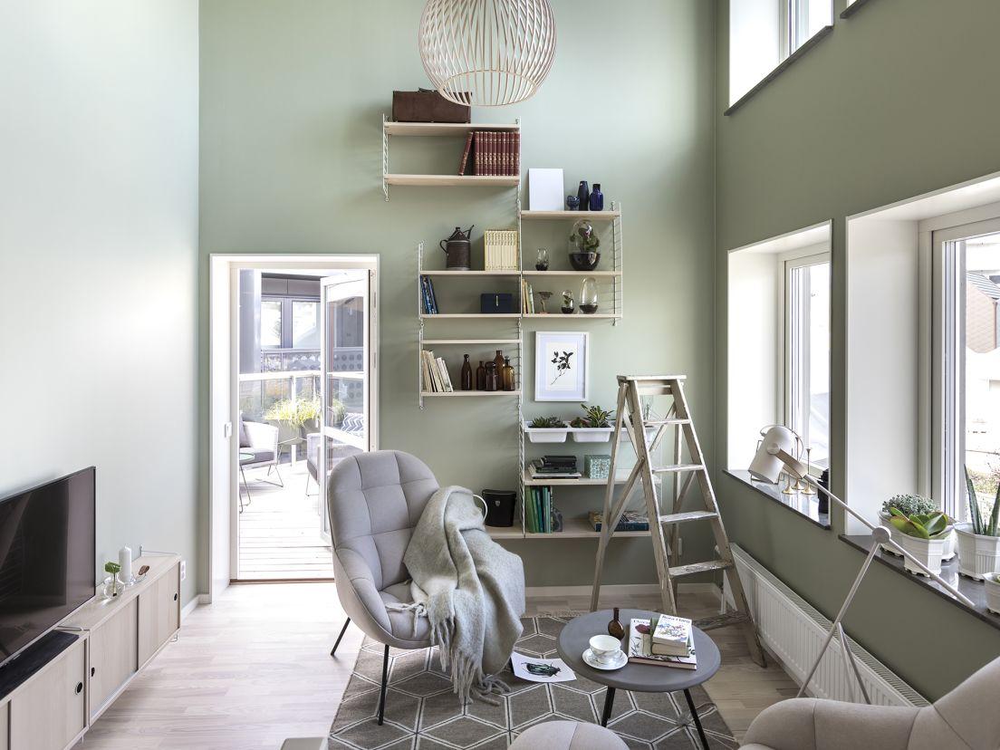 Ett vardagsrum med gröna väggar och en balkong