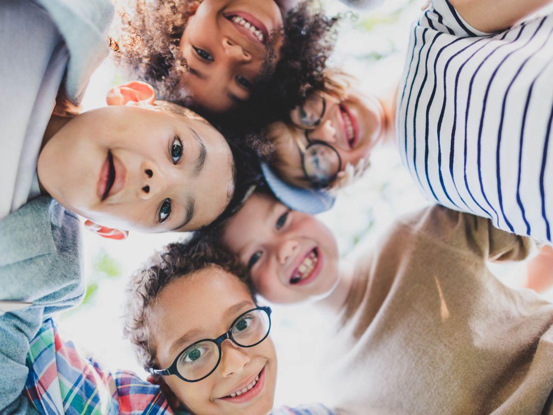 En familj skrattar och tittar in i kameran