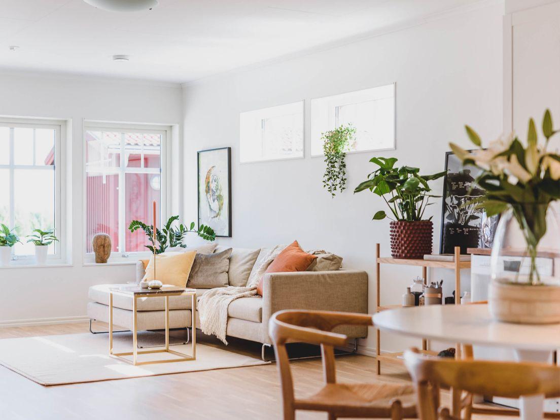 En beige soffa i ett vardagsrum med öppen planlösning