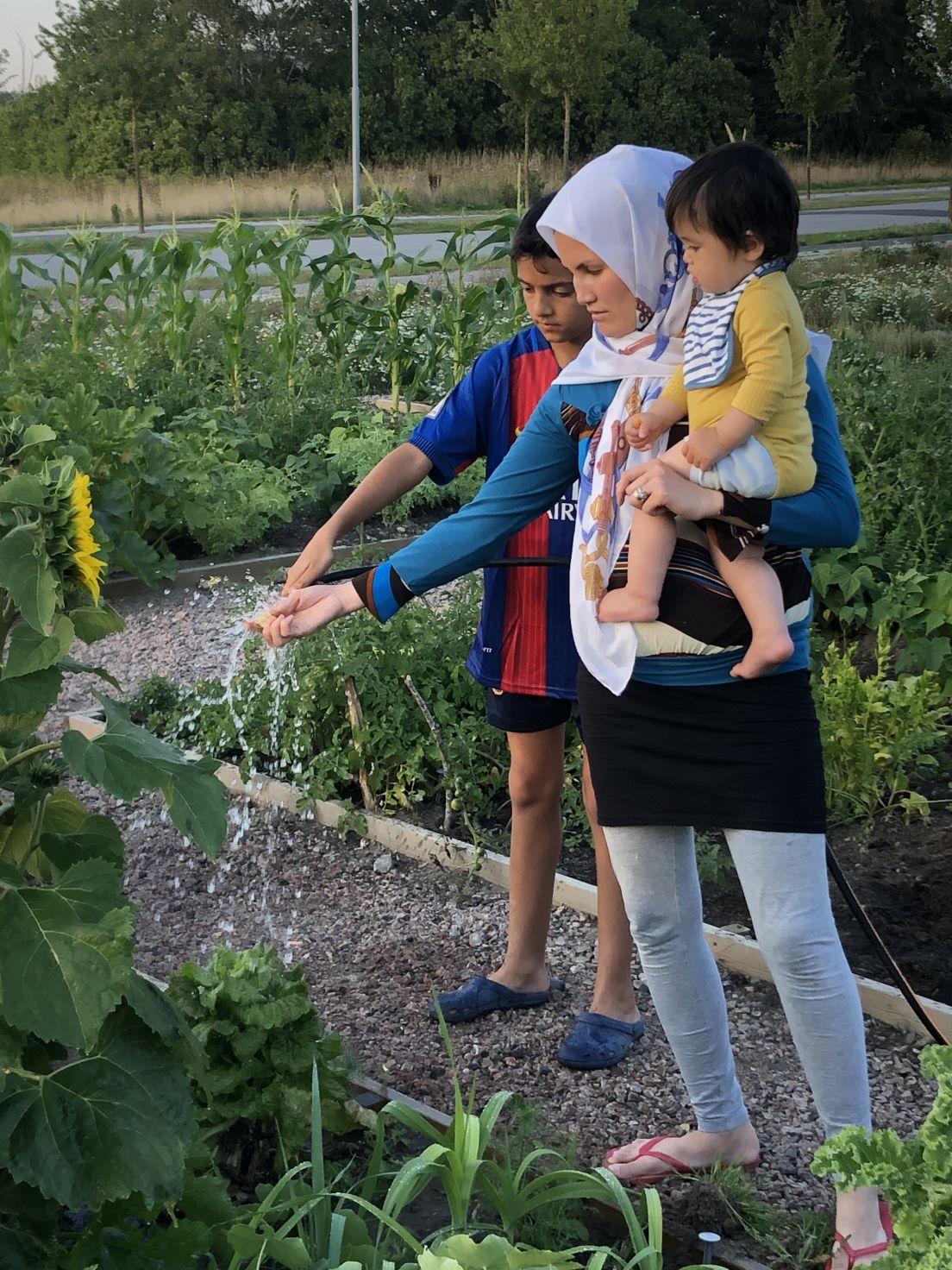 En mamma med ett barn i famnen och ett bredvid vattnar sina grödor