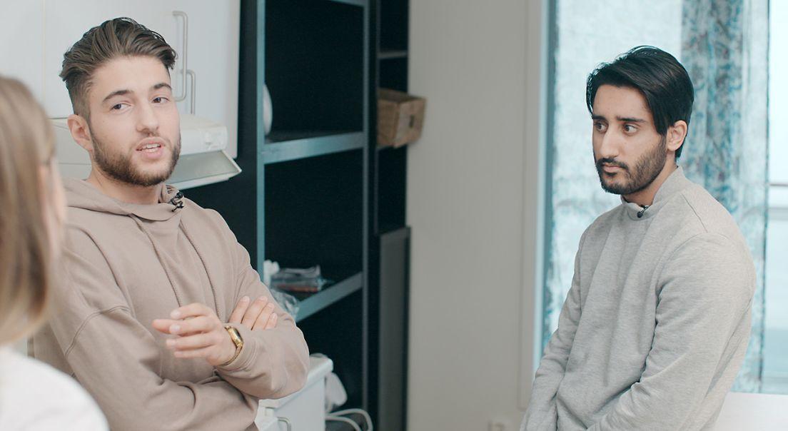 to menn i grå og beige genser snakker med kvinne