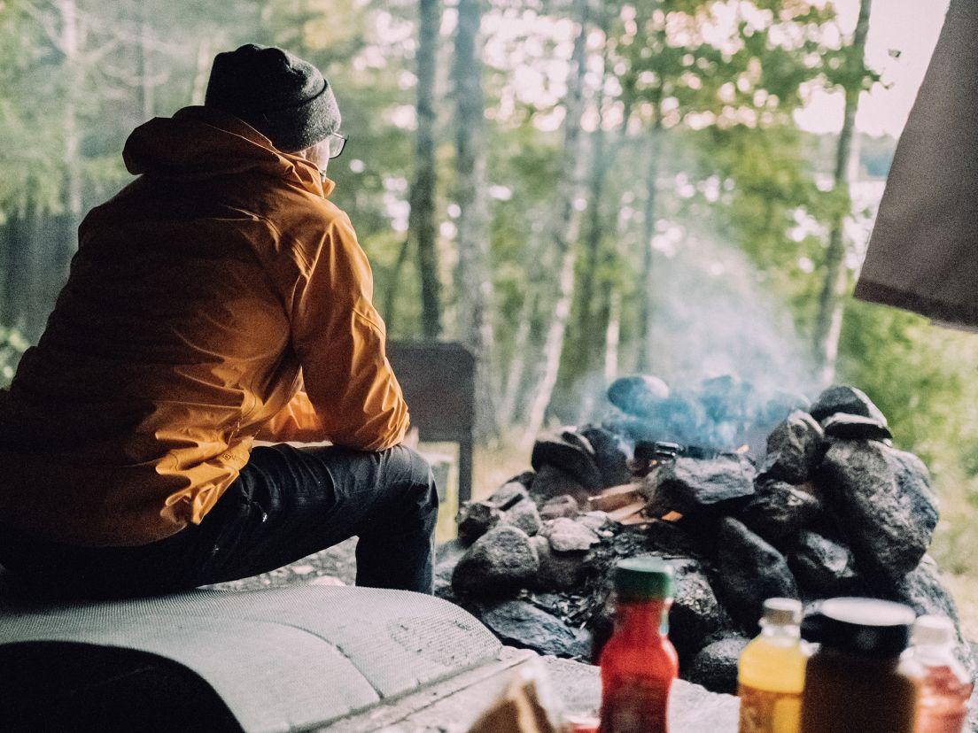 En man som grillar samtidigt som han blickar ut över en skog