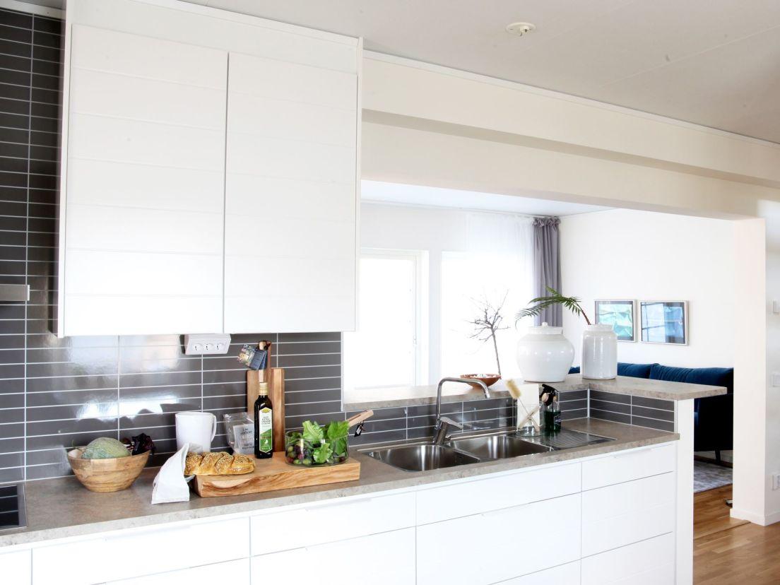 interiör kök med vita skåp och mörk kakel-vägg