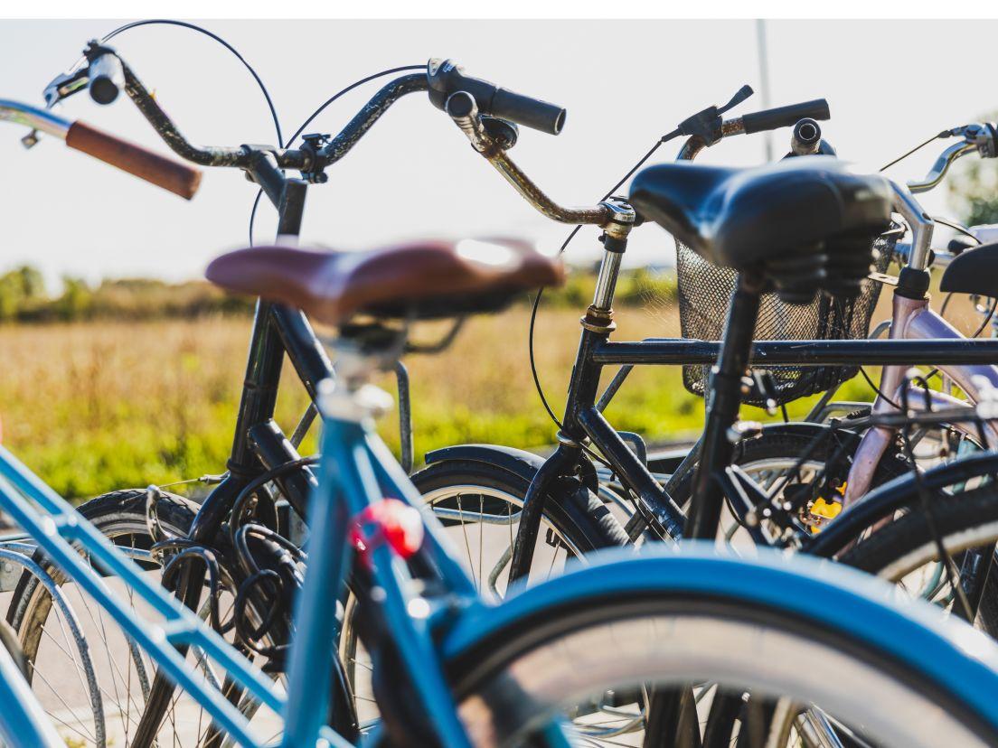 två cyklar står parkerade framför äng
