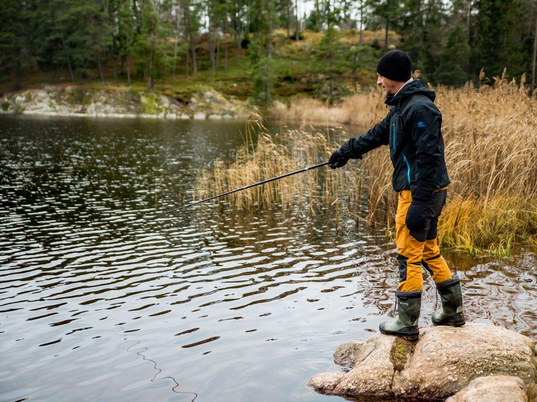 En man som fiskar i gula byxor