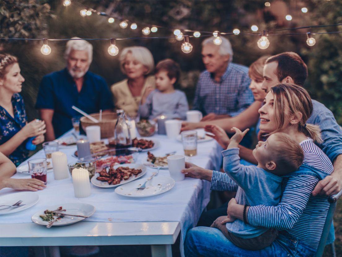 stor familj sitter ute och äter middag i trädgården