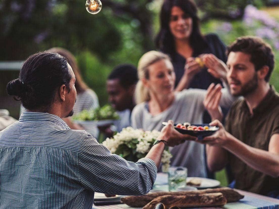 Människor som sitter utomhus en härlig sommarkväll och äter