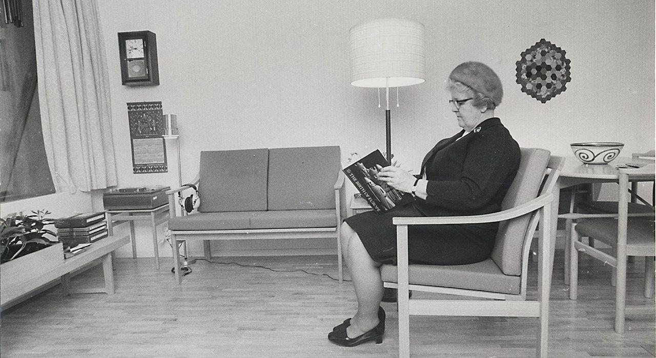 Svarthvitt bilde av en kvinne som sitter og leser.
