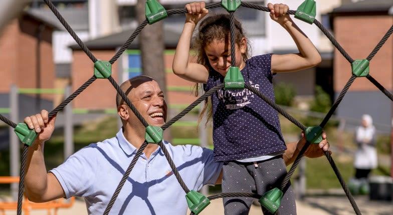 Far og datter leker i et lekestativ