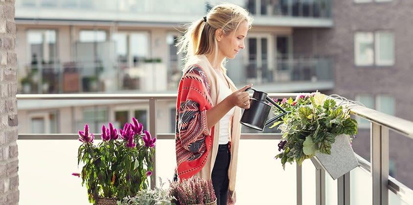 En ung dame vanner plantene på balkongen.