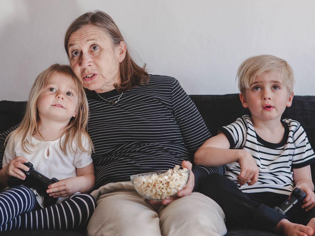 Ett barn och en äldre dam sitter tillsammans i en soffa och äter popcorn
