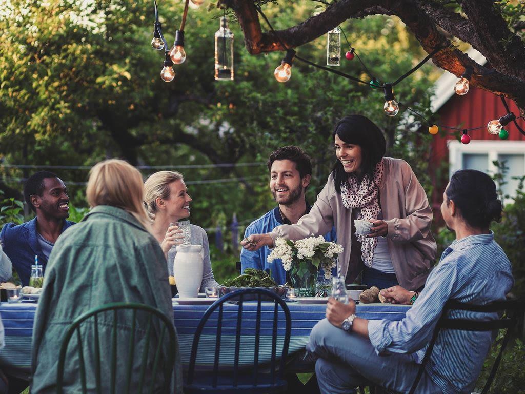 ett gäng vänner sitter ute runt ett bord i trädgården