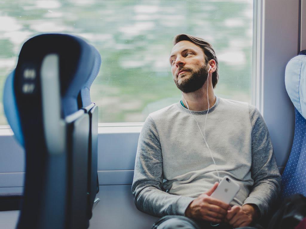 En kille sitter på en buss och lyssnar på musik