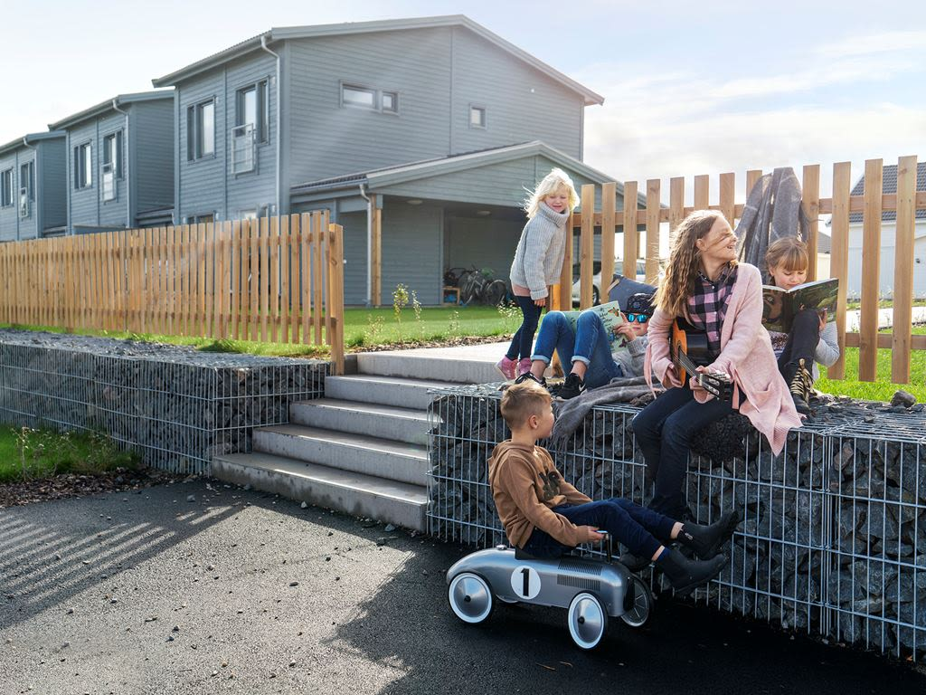 En familj leker och spelar gitarr utanför en radhuslänga