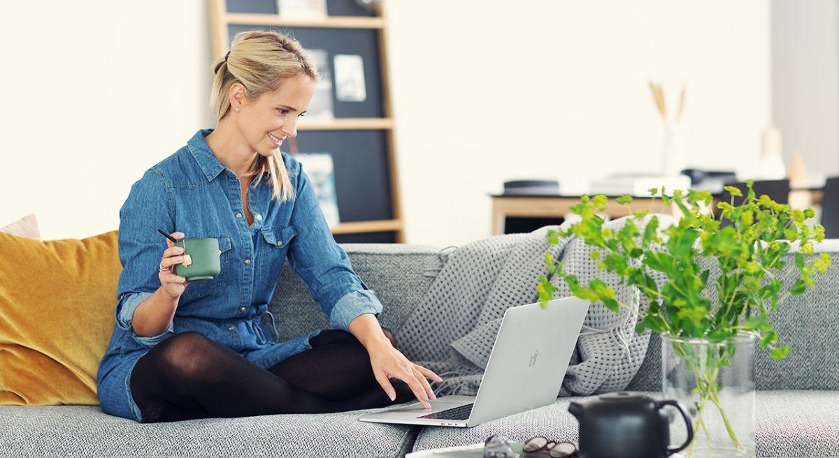 Dame i sofaen med tekopp og macbook