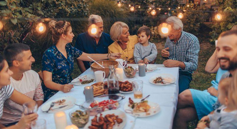 stor familie med besteforeldre og barnebarn spiser middag i hagen