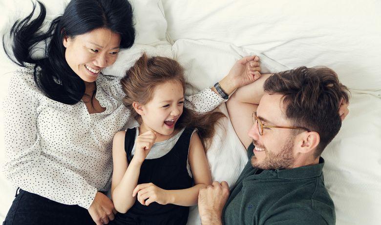 En mor, datter og far ligger i en seng og ler