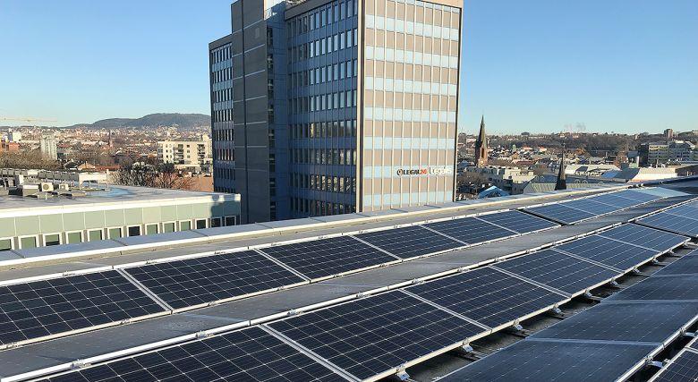 Et tak med solcellepanel med OBOS-bygg i bakgrunnen