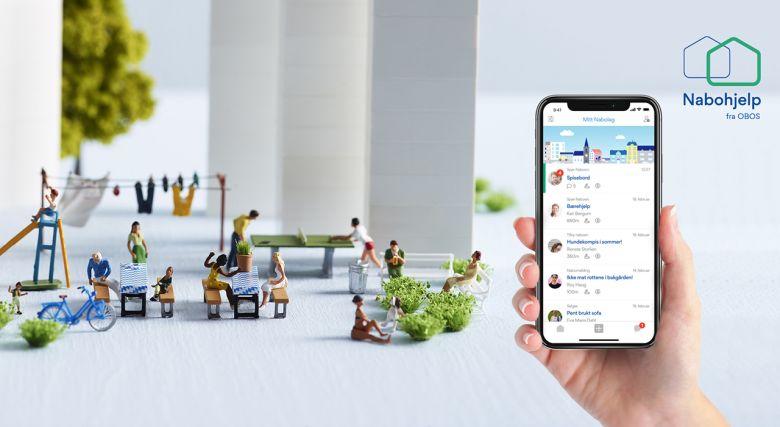 Bildet viser en hånd som holder en mobil med Nabohjelp-appen åpen. I bakgrunnen vises små figurer som sammen illustrerer et nabolag.