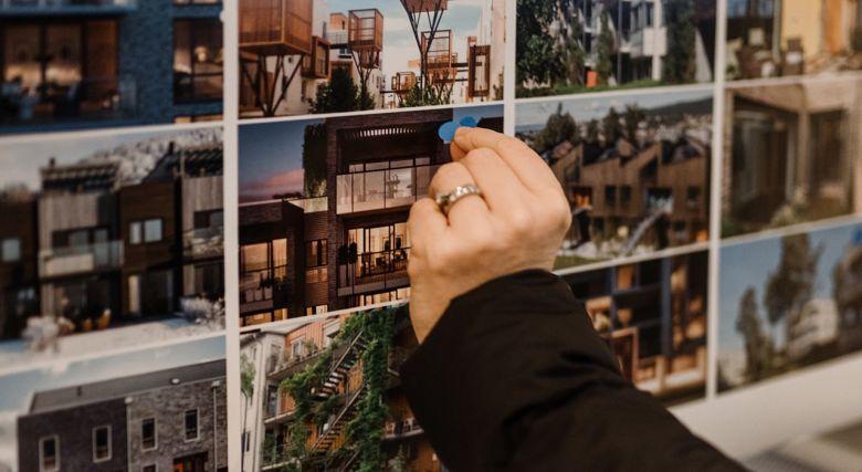 Hånd som setter klistermerker på bilder på Nabolab på Fornebu.