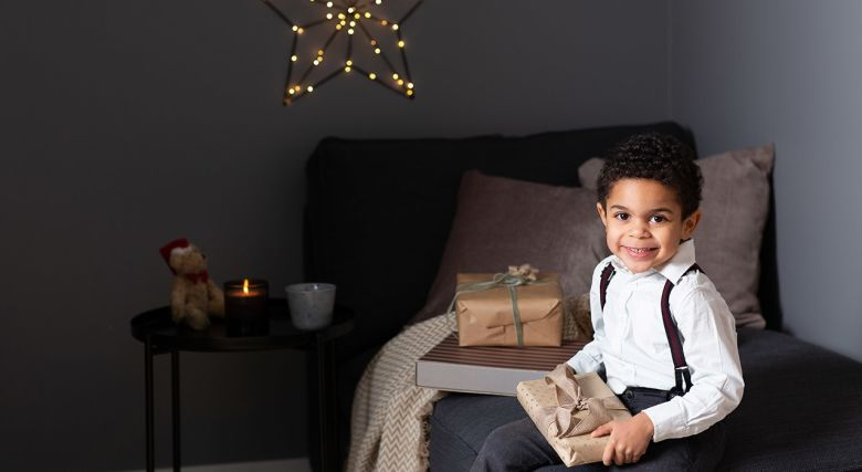 Ung gutt på soverom med julegave i fanget
