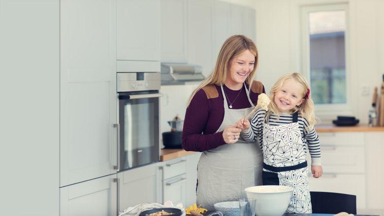 Gravid mor med et lite barn på kjøkkenet