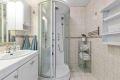 Badet er flislagt med dusjkabinett, servantinnredning. Det er separat toalett/wc i eget rom