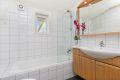 Bad med badekar og innholdsrik baderomsinnredning