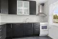 Kjøkkeninnredning med sorte fronter og takhøye overskap.