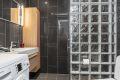 Badet har fine mørke fliser på gulv og vegger