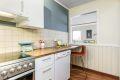 Kjøkken med hvite slette fronter og nyere benkeplate
