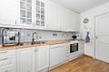 Lyst kjøkken med profilerte fronter og takhøye overskap