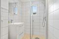 Lyst og fint fliselagt baderom bestående av wc, servant m/underskap, speil m/overlys, veggskap og innsvingbart dusjhjørne.