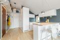 Kjøkkenet er praktisk, lyst og moderne med slette hvite flater