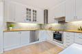 Kjøkkenet er lyst og moderne, med fine fliser over benkeplaten.