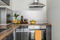 Moderne kjøkkeninnredning med grå høyglansfronter, skuffer med demper, laminert benkeplate.