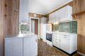 Hvit laminat innredning med fliser over kjøkkenbenk.