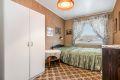 Soverom 2 med teppe på gulv, strietapet på vegger og malt tak. Garderobeskap og originalt plassbygd garderobeskap.