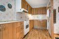 Kjøkkeninnredning med profilerte eikefronter, slette eikefronter, laminert benkeplate med fliser over, ventilator og varmtvannsbereder i underskap.