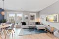 Stue med åpen kjøkkenløsning og store vinduer som slipper inn mye naturlig lys