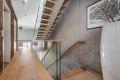 Eik trappetrinn med rekkverk av glass inn mot rå betongvegg. På veggen i gangen er det hentet tegl fra opprinnelig bygg som er tatt med inn og murt opp igjen som delevegg i den nye Town housen.